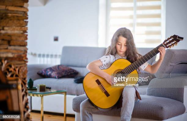 boy with classical guitar playing on the guitar - acoustic guitar stock pictures, royalty-free photos & images