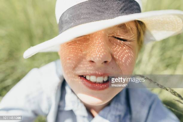 boy with closed eyes wearing a hat sitting in field - squinting stock photos and pictures