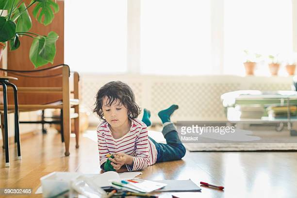 Boy with colorful felt lip pens and books lying on floor at home