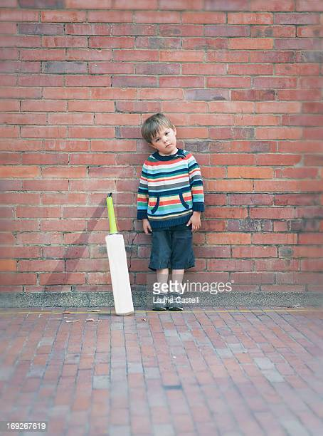 Boy with cricket bat against brick wall
