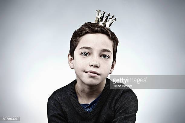 Boy with crown looking bored and unmotivated