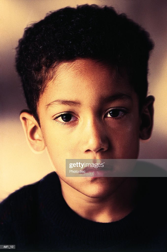 boy with dark long hair which stands up wearing a black shirt looks into the camera with a sad unhappy look : Stockfoto