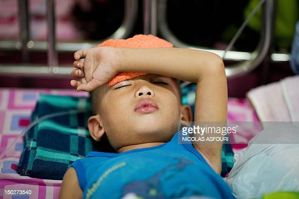 A boy with dengue disease sleep on a bed at the Quirino hospital in Manila on August 14 2012 Philippine authorities rushed relief supplies to the...
