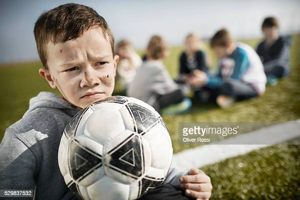 Boy with dirty face on soccer field