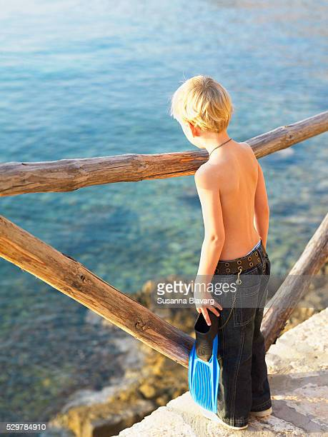 Boy with diving flippers in his hand looking down into the water.