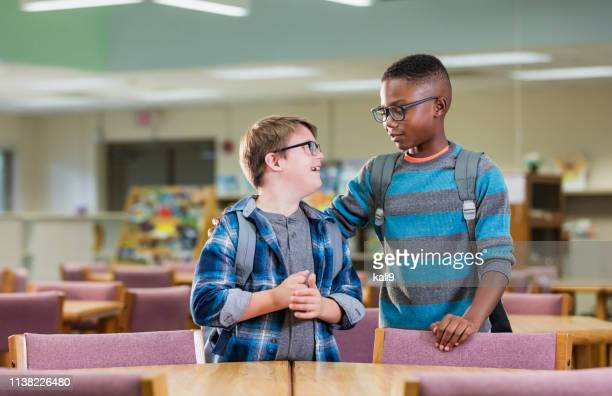 boy with down syndrome and friend in school library - learning disability stock pictures, royalty-free photos & images