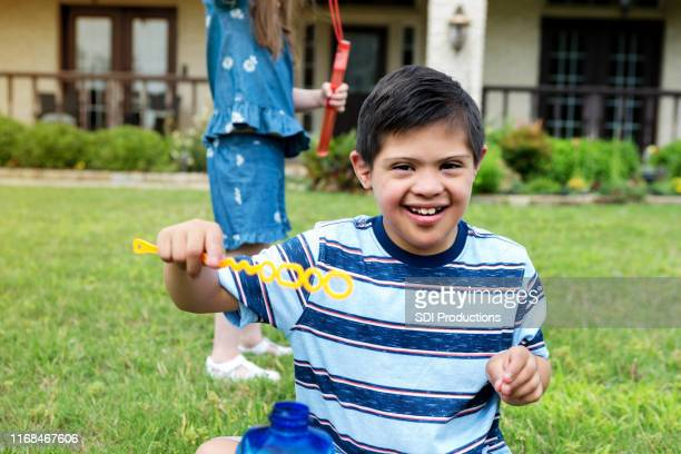 boy with down syndrome and unrecognizable sister play bubbles - intellectually disabled stock pictures, royalty-free photos & images