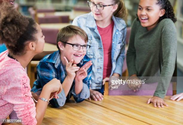 boy with down syndrome, classmates in school library - learning disability stock pictures, royalty-free photos & images