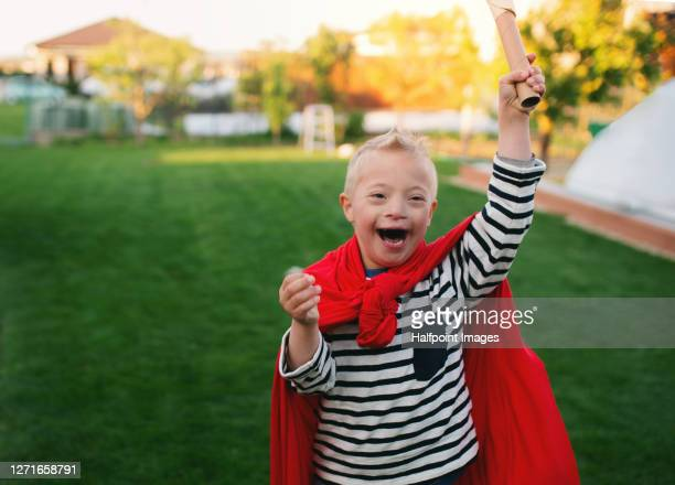 boy with down syndrome playing outdoors in garden. - physical disability stock pictures, royalty-free photos & images