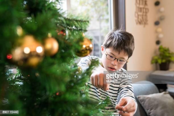 ダウン症候群を持つ少年がクリスマス ツリーを飾る