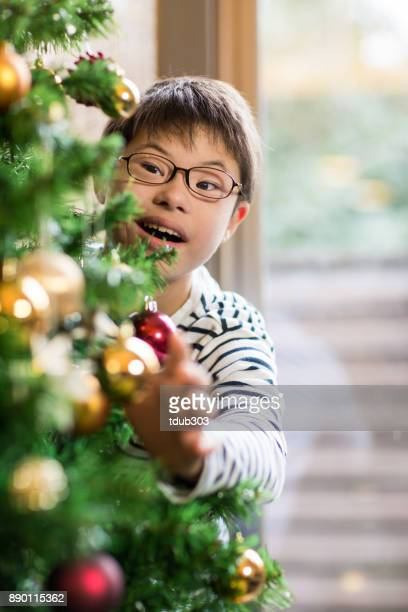 A boy with Downs syndrome hanging decorations on a Christmas tree