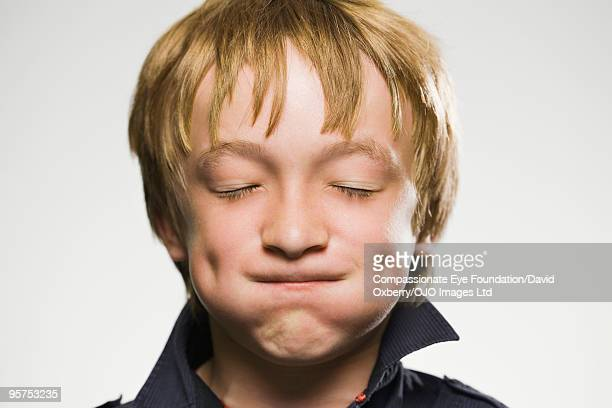 Boy with eyes closed puffing out his cheeks