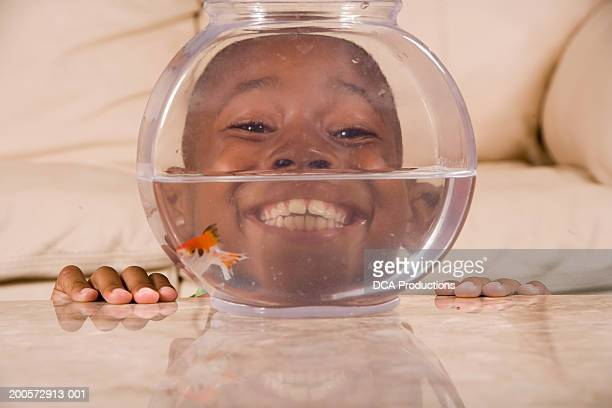 Boy (6-7) with face behind goldfish bowl, smiling, portrait