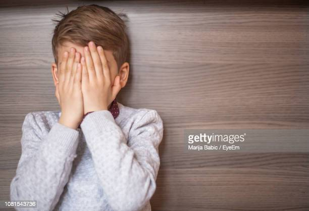 boy with face covered by hands against wooden wall - marija mauer stock-fotos und bilder