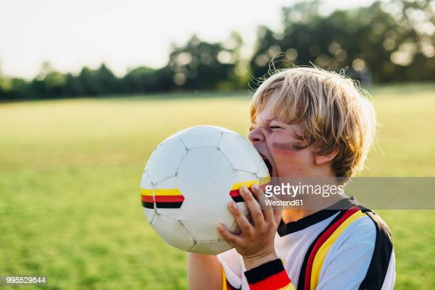 boy with face paint and german football shirt, biting soccer ball - 噛む ストックフォトと画像