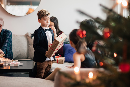 Boy with family looking at Christmas presents in living room - gettyimageskorea
