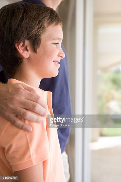Boy with father's hand on his shoulder