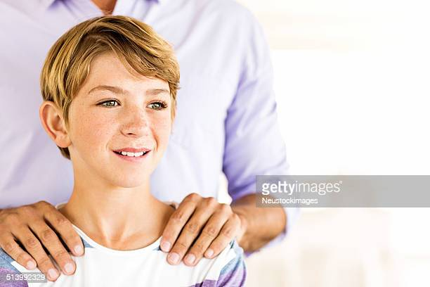 Boy With Father's Hand On His Shoulders Looking Away