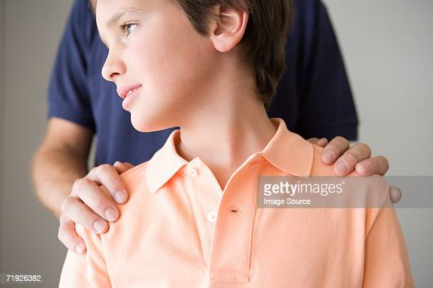 Boy with father's hand on shoulders