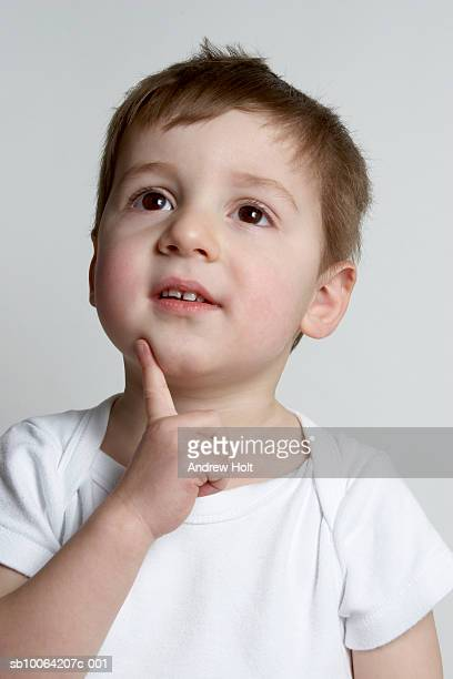 boy (4-5) with finger to chin, studio shot, close-up - andrew chin stock pictures, royalty-free photos & images