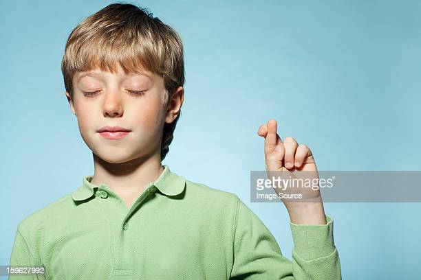 Boy with fingers crossed