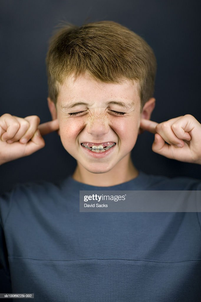 Boy (6-7) with fingers in ears, close-up : Stockfoto