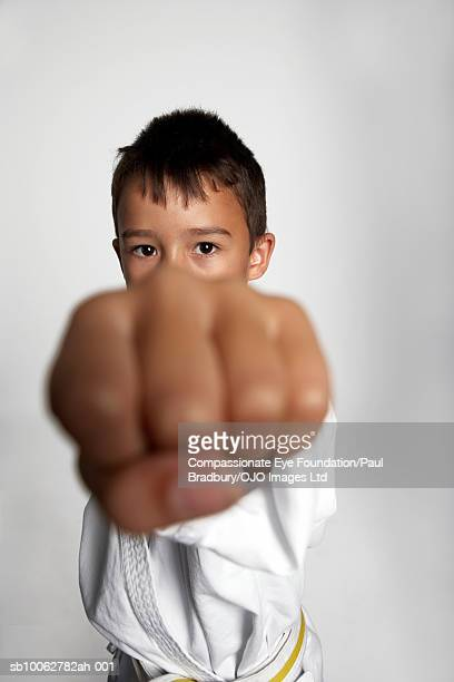 Boy (6-7) with fist clenched in front of camera, portrait (focus on face)