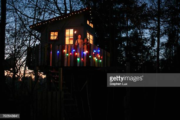 Boy with flame torch and his brother looking out from treehouse balcony at night