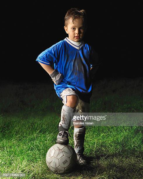 Boy (4-6) with foot on football, hands on hips, portrait