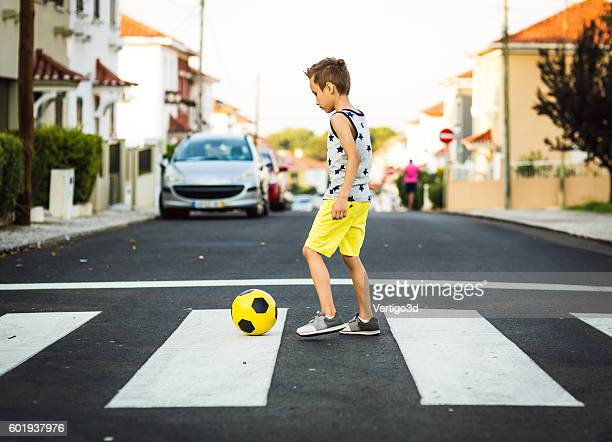 Boy with  football ball on the road