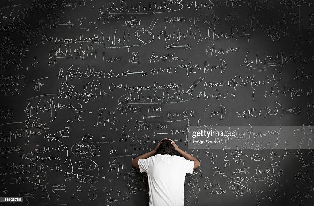 Boy with formulae on blackboard : Stock-Foto