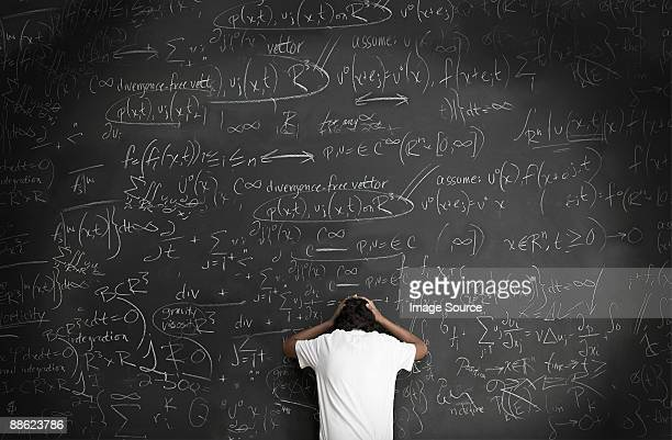 Boy with formulae on blackboard