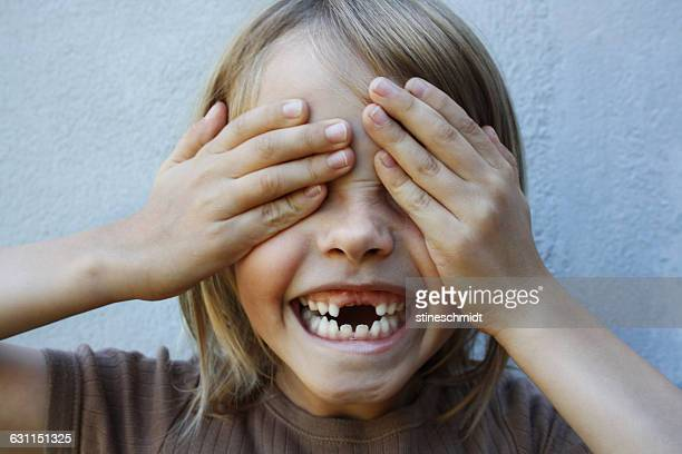 Boy with gap toothed smile with hands covering eyes