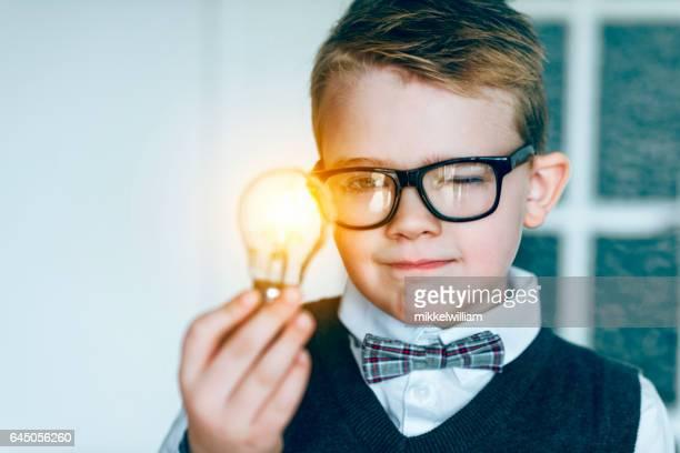 Jongen met bril en bow tie kijkt naar gloeiende gloeilamp en krijgt een idee