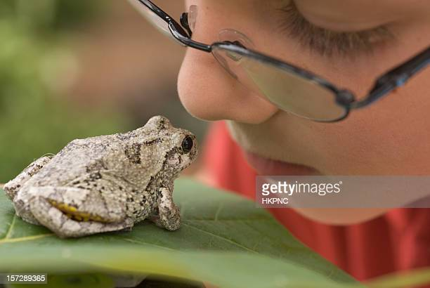 Boy With Glasses Looking At Frog on Leaf Outside
