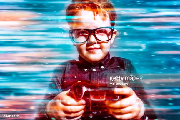 Boy with glasses plays video game and cheers as he wins
