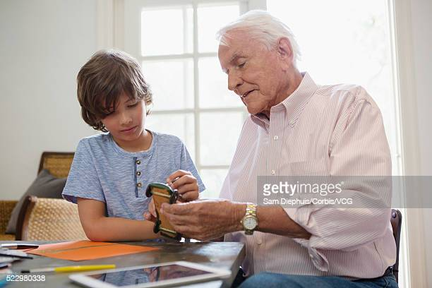 Boy (8-9) with grandfather coloring toy racecar at table