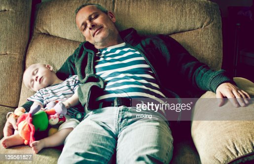 Boy with grandfather sleeping on sofa