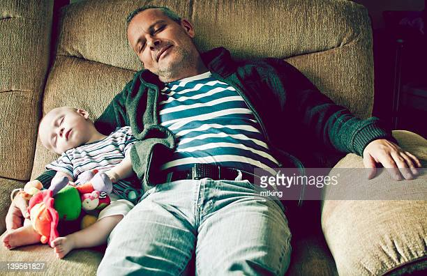 Boy with grandfather sleeping on sofa