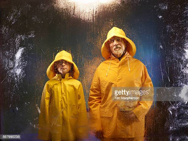 Boy with Grandfather stand wearing waterproofs