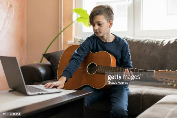 boy with guitar using laptop - tutorial stock pictures, royalty-free photos & images