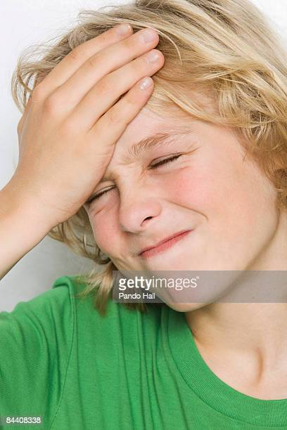 Boy (10-11) with hand on forehead, eyes closed