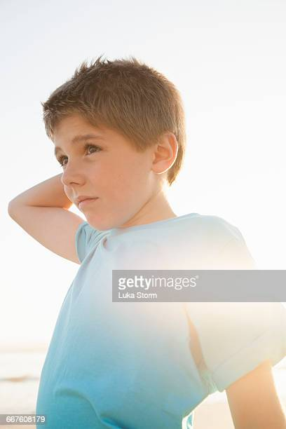 Boy with hand on head looking away