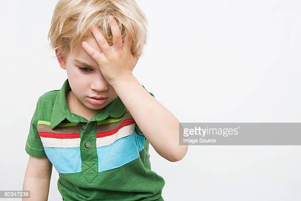 Boy with hand on head