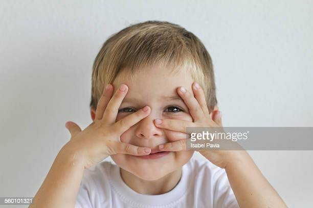 Boy with hand over face, peeking through fingers