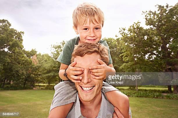 boy (4-5) with hand over fathers eyes - augen zuhalten stock-fotos und bilder