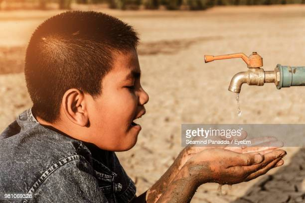 boy with hands cupped under faucet on drought land - drought stock pictures, royalty-free photos & images