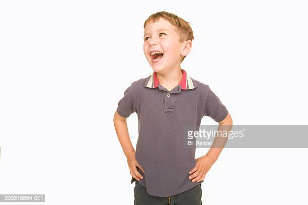 boy (4-6) with hands on hips, looking up, smiling - arms akimbo stock pictures, royalty-free photos & images