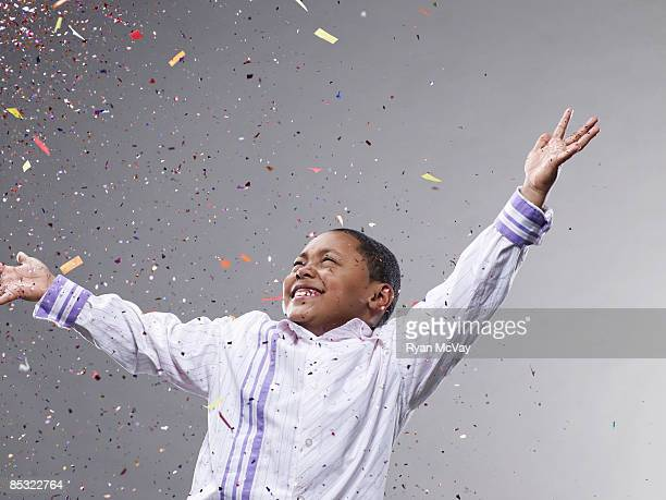 Boy with hands up, confetti flying
