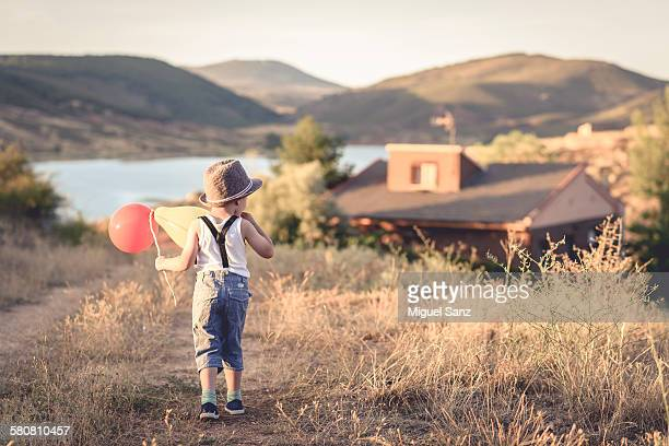 boy with hat and balloons walking on the trail - liguero fotografías e imágenes de stock